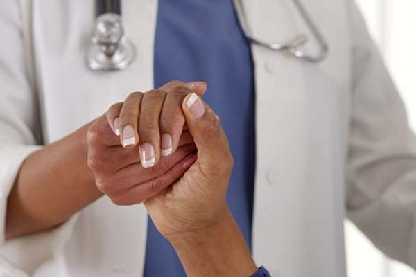 Close up of female African American doctor holding patient's hand